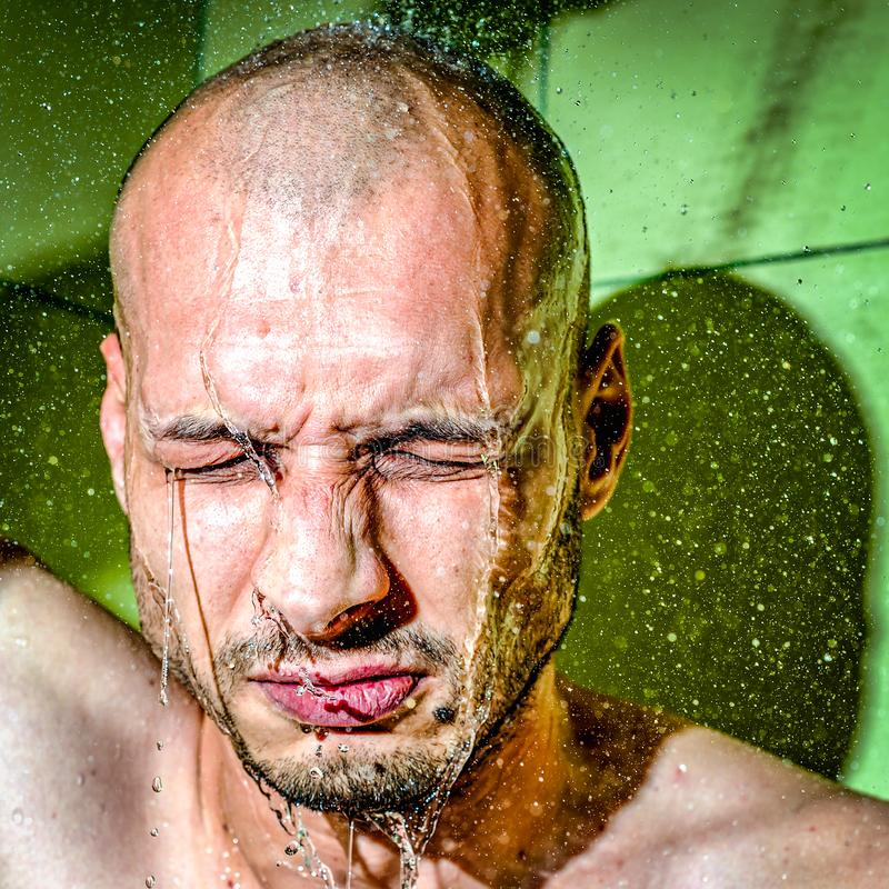 A man gives himself a cold shower after work to calm down after hard frustrated and nervous day at his job close up royalty free stock image