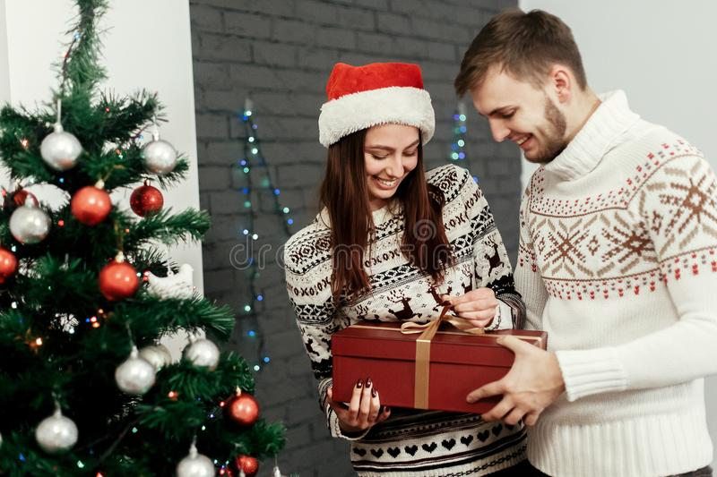 Man giving big present to his woman. happy stylish family smiling at decorated christmas tree. joyful cozy moments in winter. Holidays. seasonal greetings stock images