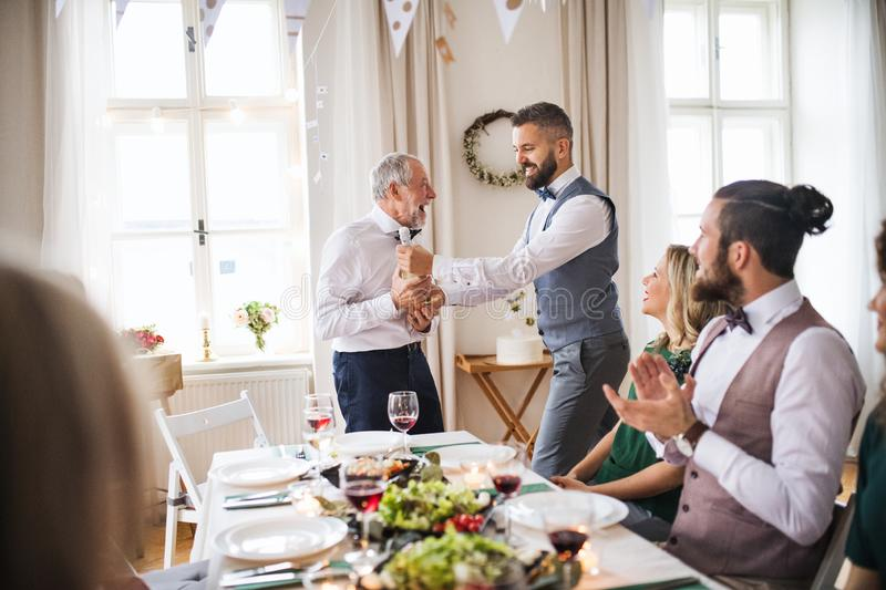A man giving a bottle of wine to his father on indoor birthday party, a celebration concept. stock photo