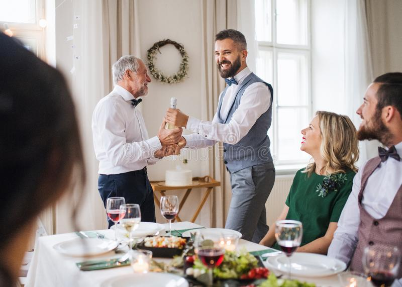A man giving a bottle of wine to his father on indoor birthday party, a celebration concept. stock photography