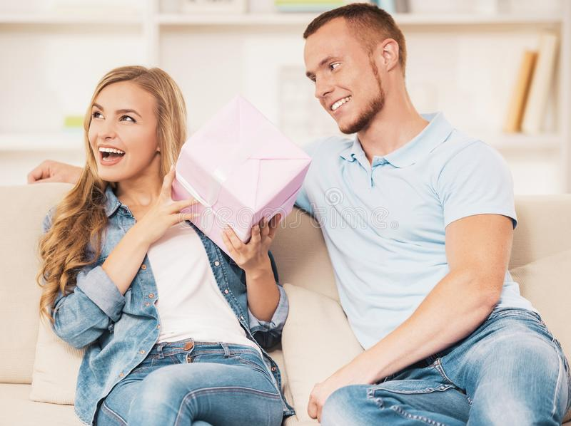Man Giving Box with Present to Cheerful Girlfriend. royalty free stock images