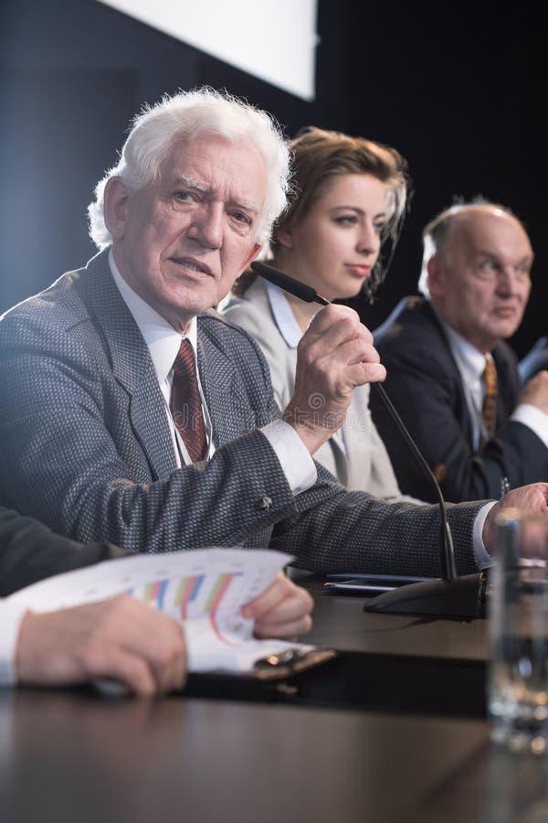 Man giving corporate presentation. Mature businessman giving corporate presentation at desk royalty free stock photo