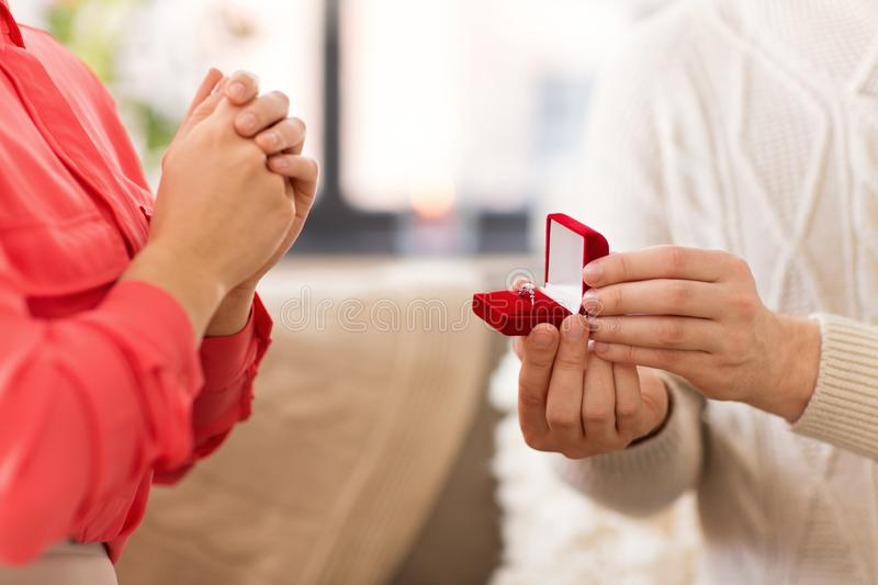 Man giving diamond ring to woman on valentines day. Valentines day, proposal and engagement concept - man giving diamond ring in little red gift box to woman at stock image