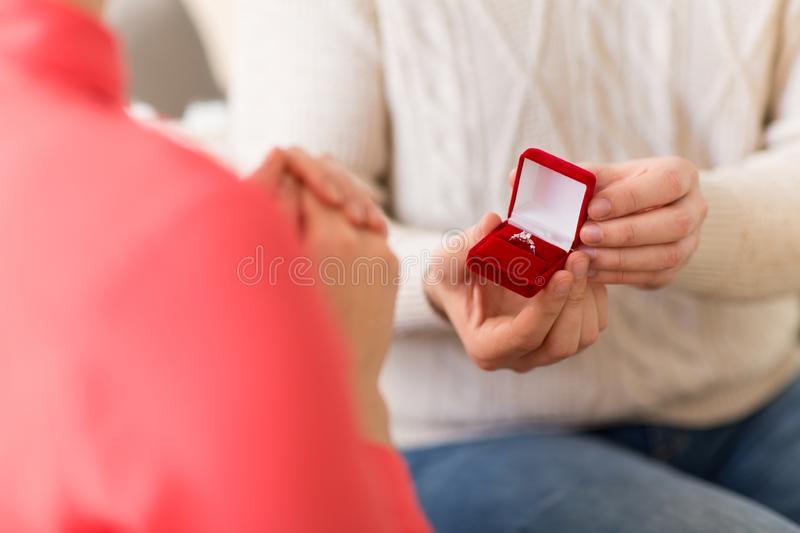 Man giving diamond ring to woman on valentines day. Valentines day, proposal and engagement concept - man giving diamond ring in little red gift box to woman at royalty free stock image