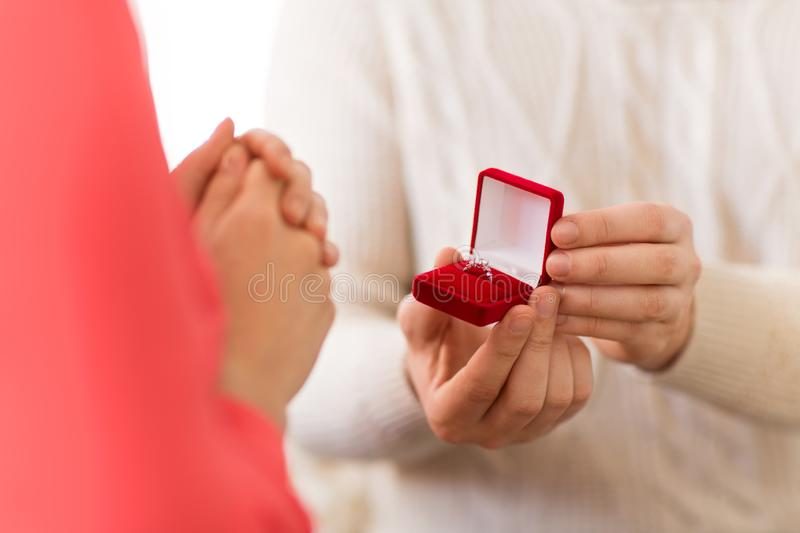 Man giving diamond ring to woman on valentines day. Valentines day, proposal and engagement concept - man giving diamond ring in little red gift box to woman at stock photos