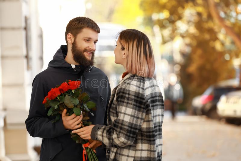 Man giving flowers to his girlfriend during romantic date outdoors stock image