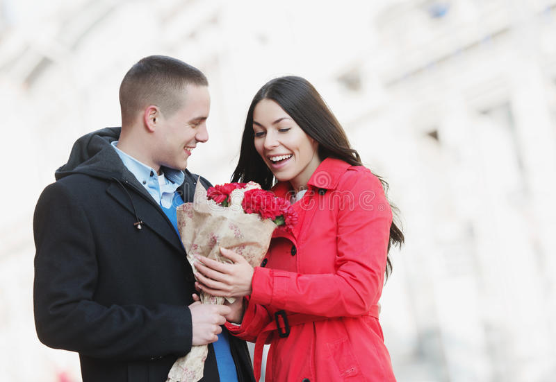 Man giving flowers to his girlfriend; young, romantic couple outdoors royalty free stock image