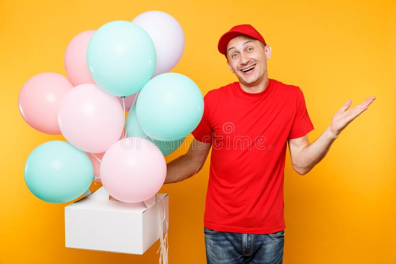 Man giving food order cake box on yellow background. Male employee courier in red cap t-shirt hold colorful air. Balloons, dessert in empty cardboard box royalty free stock photos