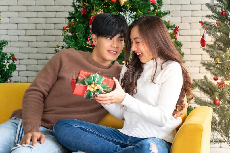 Man giving girl christmas present. Beautiful happy asian girl opening christmas present gift box from her boyfriend for Christmas holiday season greeting royalty free stock image