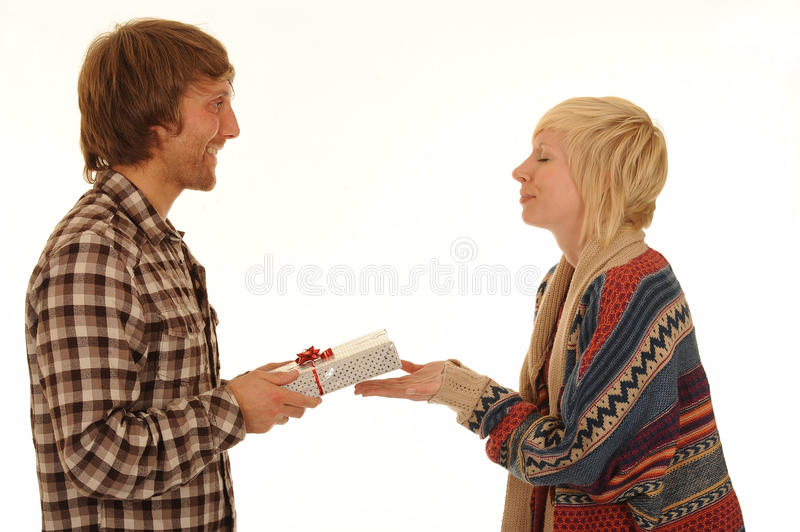 Man giving girlfriend present. Side view of happy young man giving blond girlfriend with eyes closed shut, isolated on white background royalty free stock images