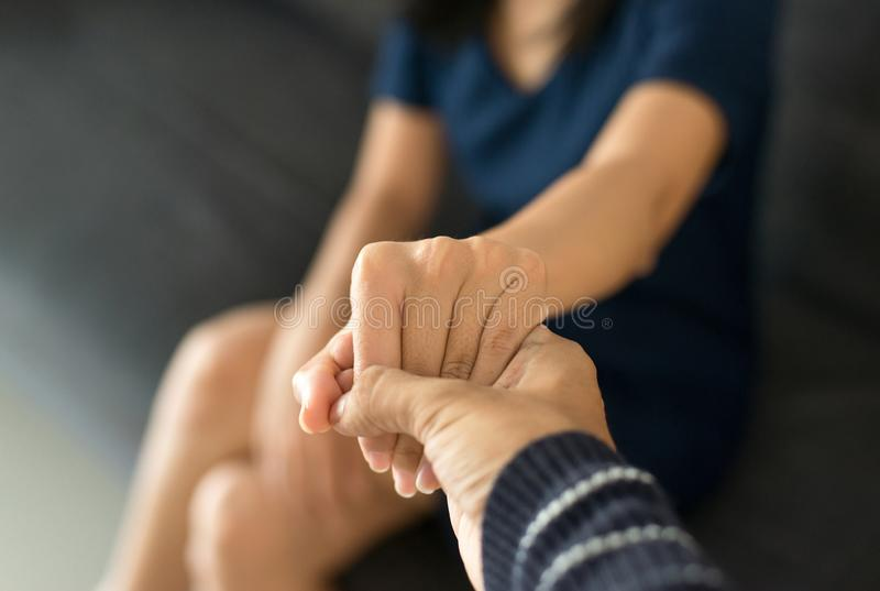 Man giving hand to depressed woman,Psychiatrist holding hands patient,Mental health care concept,Sincere feelings. Man giving hands to depressed woman stock images