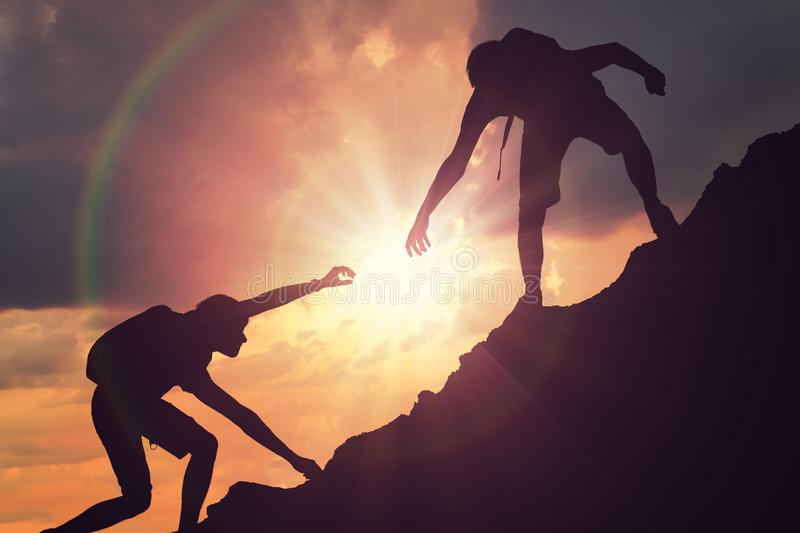 Man is giving helping hand. Silhouettes of people climbing on mountain at sunset.  stock image