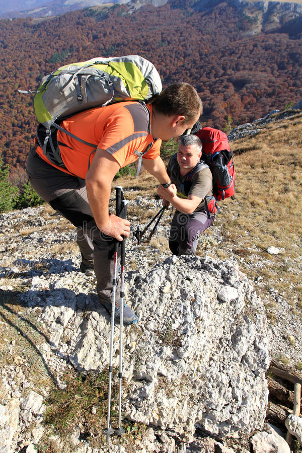 Man giving helping hand to friend to climb mountain rock cliff. Crimea Ukraine royalty free stock photo