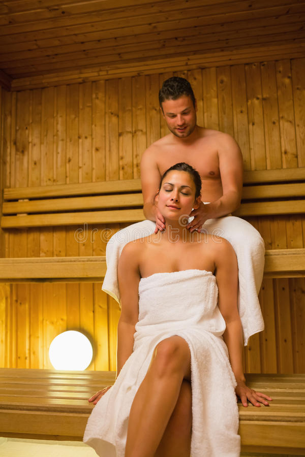 Man giving his girlfriend a neck massage in sauna. Wearing white towels and smiling stock image