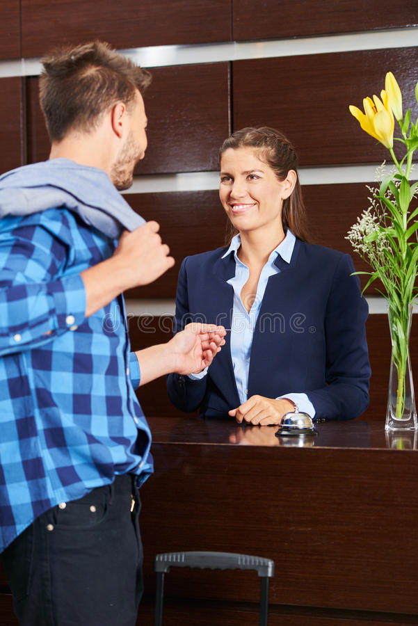 Man giving key card to hotel receptionist stock photo