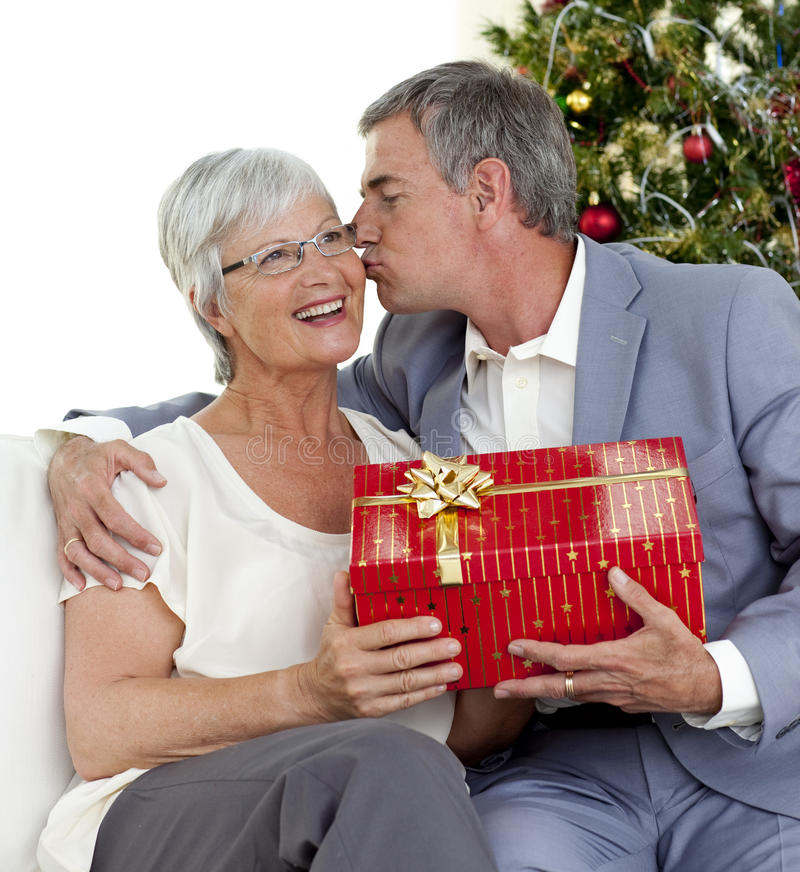 Man giving a kiss and Christmas gift to his wife. Senior man giving a kiss and a Christmas present to his wife at home royalty free stock image