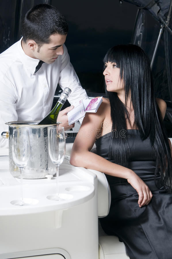 Man giving money to a woman in a bar. Man giving money to a woman in a night club bar royalty free stock images