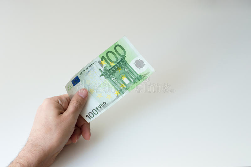 Man giving one hundred Euro banknote. Man holding one hundred Euro banknote in his hands royalty free stock image