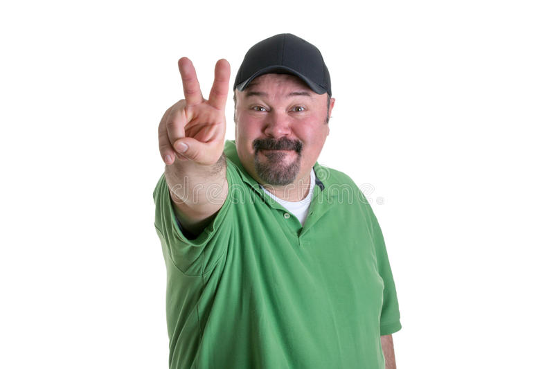 Man Giving Peace Sign Hand Gesture. Portrait of Overweight Man with Goatee Wearing Green Shirt and Black Baseball Cap Smiling and Giving Peace Sign Hand Gesture royalty free stock images