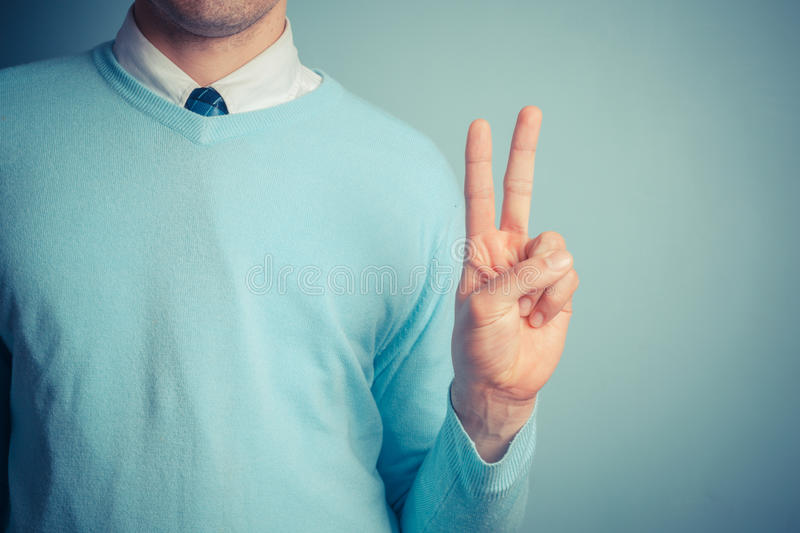 Man giving peace sign. A young man is gesturing a peace sign stock photos