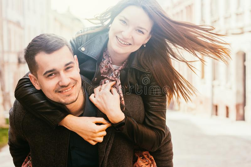 Man giving piggyback ride to his girlfriend. Happy couple in street stock images