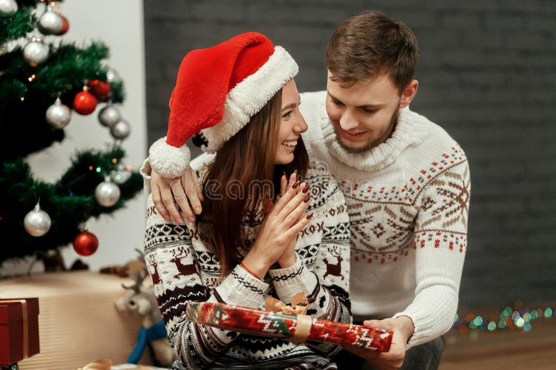 Man giving present to his woman. joyful cozy moments in winter h. Olidays. happy stylish family smiling at decorated christmas tree. seasonal greetings concept royalty free stock image