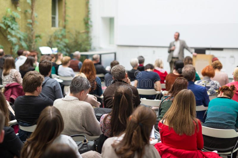 Man giving presentation in lecture hall at university. royalty free stock images