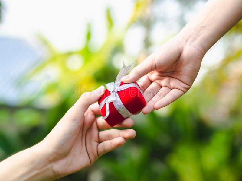Man giving a red gift box to woman. Love, Valentine,Present Concept royalty free stock image