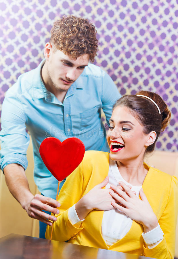 Man giving a red heart to a beautiful young woman royalty free stock image