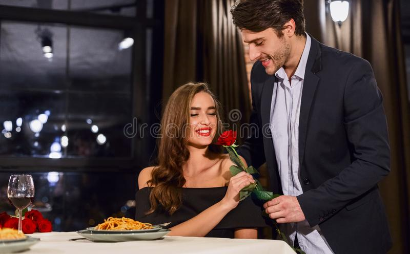 Man giving rose to his girlfriend stock image