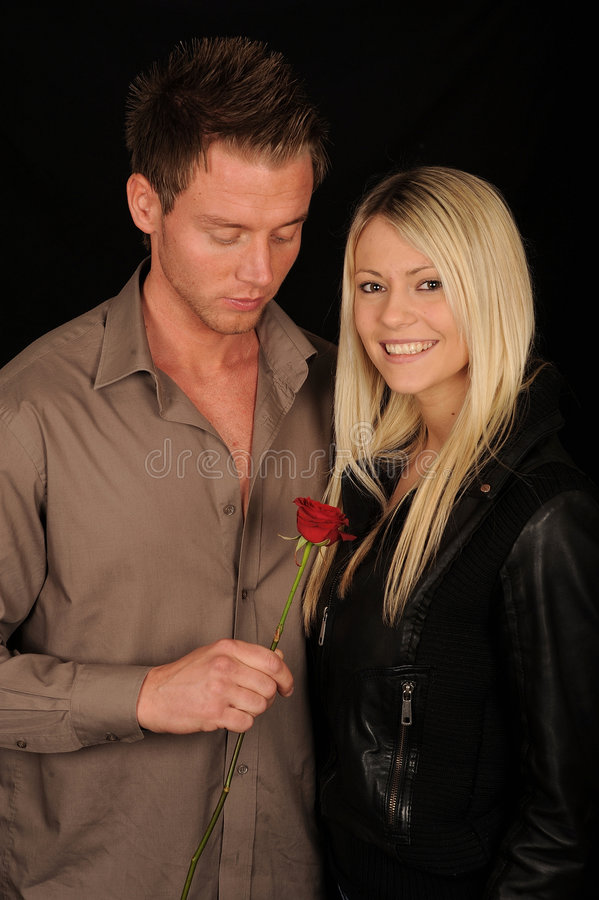 Man giving rose to woman stock photos