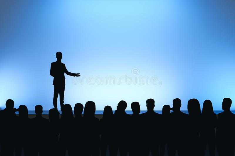 Man giving speech. In front of backlit audience on light blue background. Speaker and leadership concept royalty free stock photo
