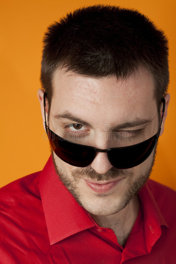 Man giving a wink over sunglasses stock photos