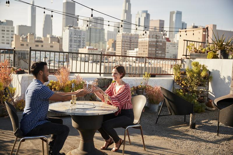 Man Giving Woman Gift As They Celebrate On Rooftop Terrace With City Skyline In Background royalty free stock images