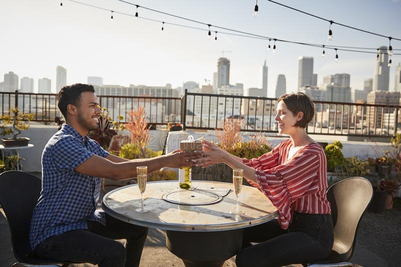 Man Giving Woman Gift As They Celebrate On Rooftop Terrace With City Skyline In Background royalty free stock photography