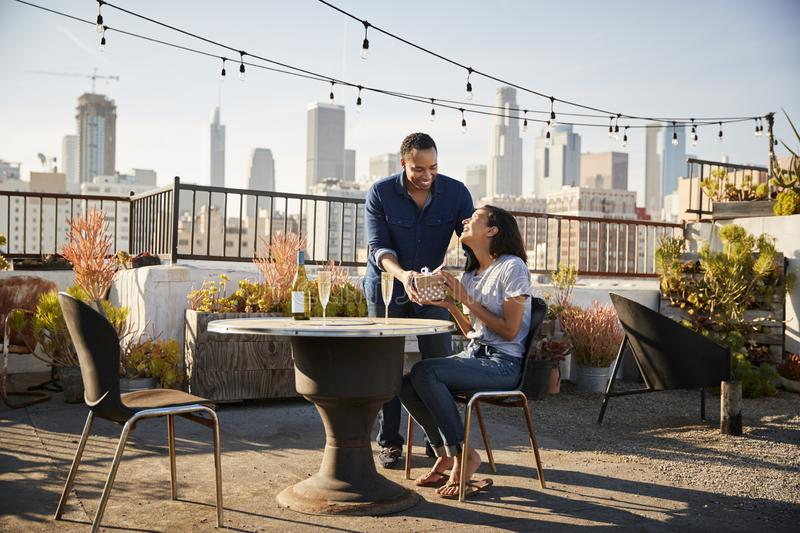 Man Giving Woman Gift As They Celebrate On Rooftop Terrace With City Skyline In Background stock photos