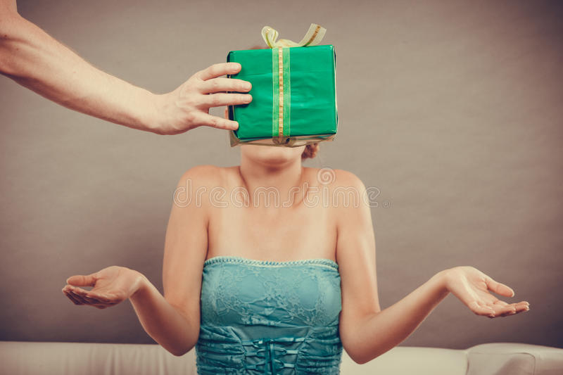 Man giving woman gift box. Male hand holding green gift box, men giving women present, girl gesturing surprised unusual view filtered photo royalty free stock image