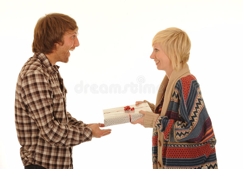 Man giving woman present. Side half body portrait of young man in casual clothes giving happy woman wrapped present of gift, isolated on white background stock photography