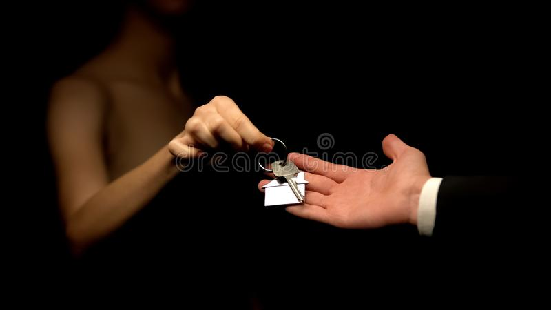 Man giving woman keys with house keychain, present for mistress, cheating stock photos