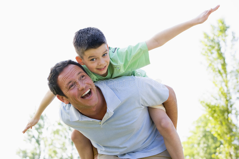 Man giving young boy piggyback ride smiling royalty free stock images