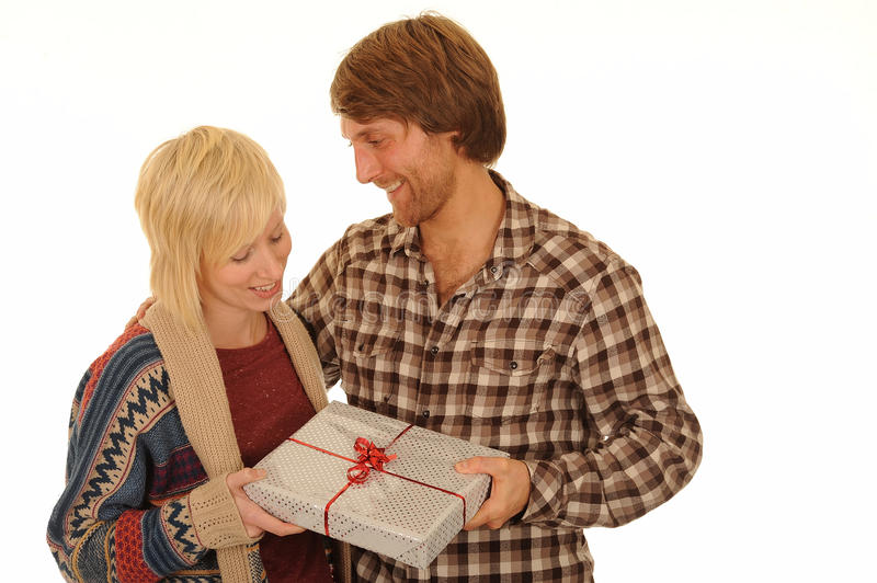 Man giving young woman gift. Handsome young man giving gift of present to happy young blond woman, isolated on white background stock image