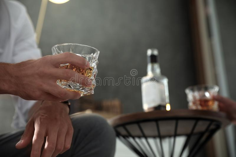 Man with glass of  indoors, closeup view. Space for text. Man with glass of whiskey indoors, closeup view. Space for text royalty free stock images