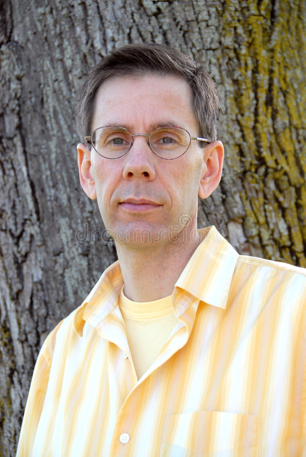 Man With Glasses. Man wearing glasses standing against a tree royalty free stock photos