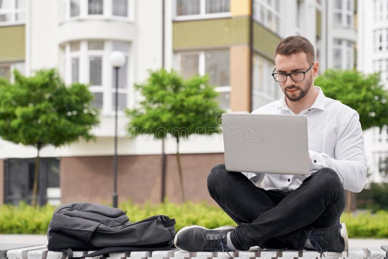 Man in glasses on bench holding laptop on knees, working. royalty free stock photos