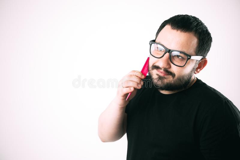 Man with glasses combing his beard with a pink comb. Brutal man with glasses combing his beard with a pink comb royalty free stock image