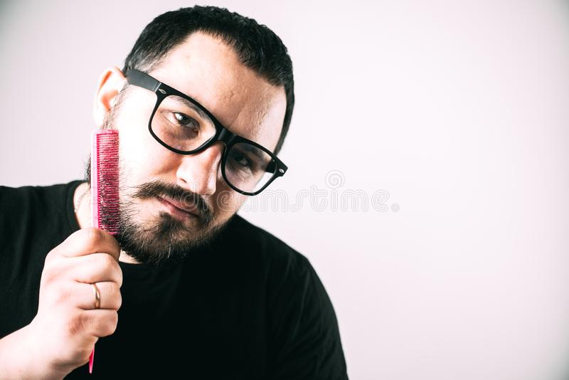 Man with glasses combing his beard with a pink comb. Brutal man with glasses combing his beard with a pink comb royalty free stock photo