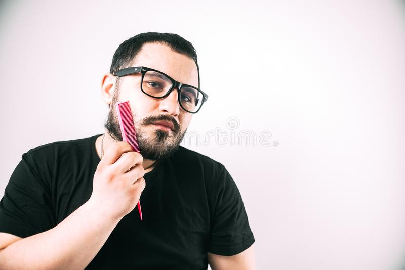 Man with glasses combing his beard with a pink comb. Brutal man with glasses combing his beard with a pink comb stock image