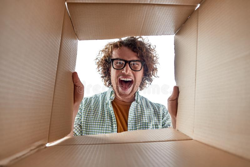 Man in glasses looking inside box stock photo