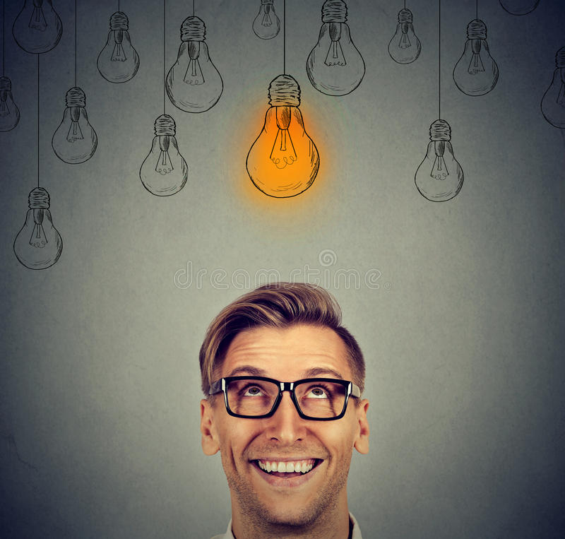 Man in glasses looking up at bright idea light bulb above head. Portrait happy handsome man in glasses looking up at bright idea light bulb above head on gray royalty free stock image
