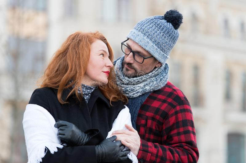 Guy in looks to woman face. Husband embraces wife on street. Urban family on street look into eyes. Sweet emotion stock photo